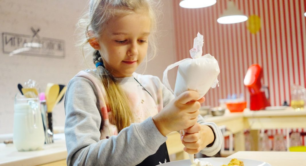 девочка делает печенье