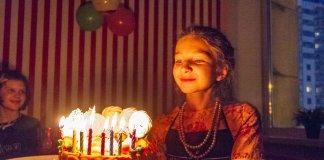 задувает свечи в торту
